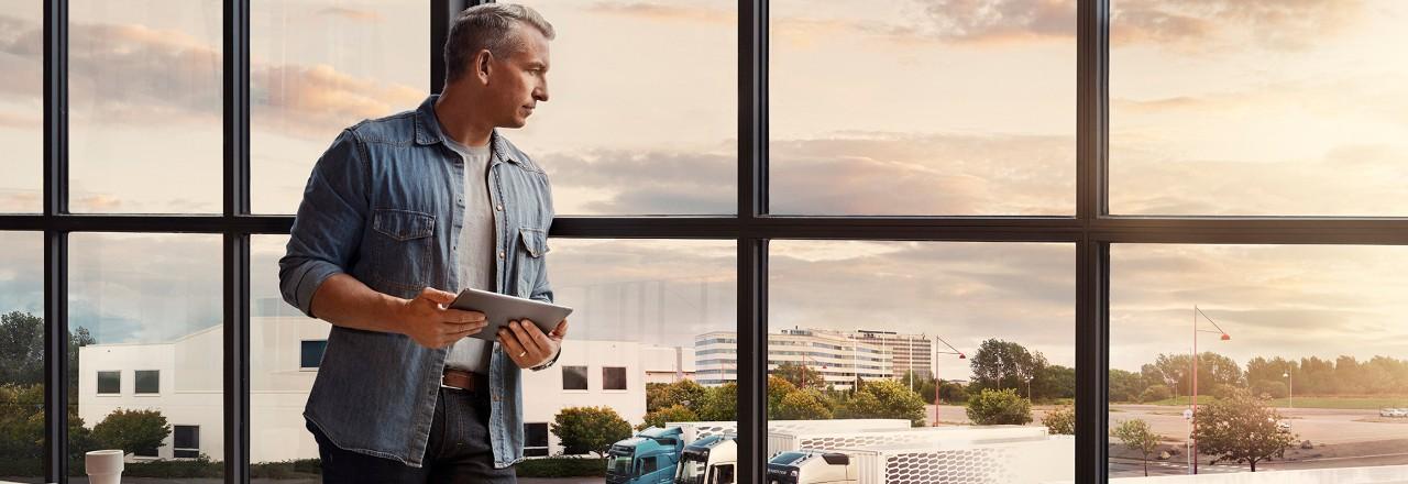 Un uomo con in mano un tablet si trova vicino a una finestra e guarda la sua flotta di camion