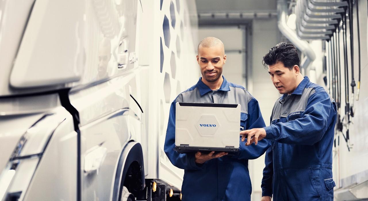 Due tecnici dell'assistenza Volvo guardano un laptop mentre si trovano accanto a un veicolo