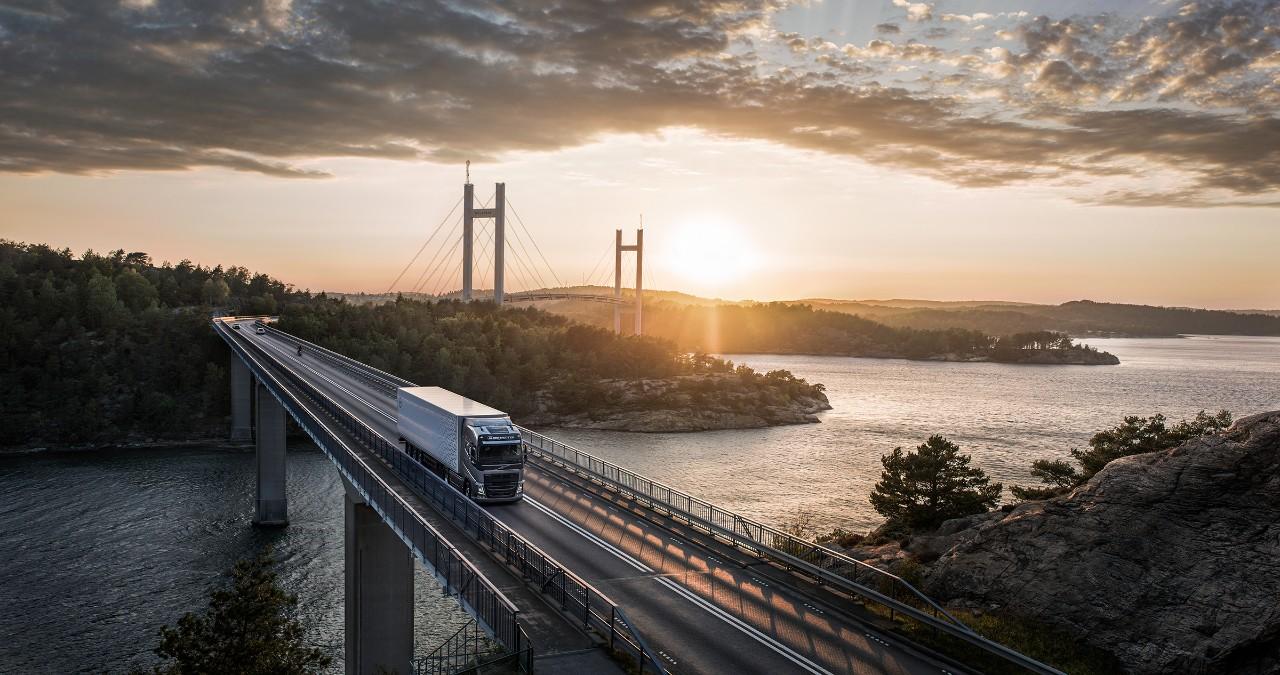 Un veicolo Volvo viaggia su un ponte sull'acqua mentre il sole tramonta dietro di esso